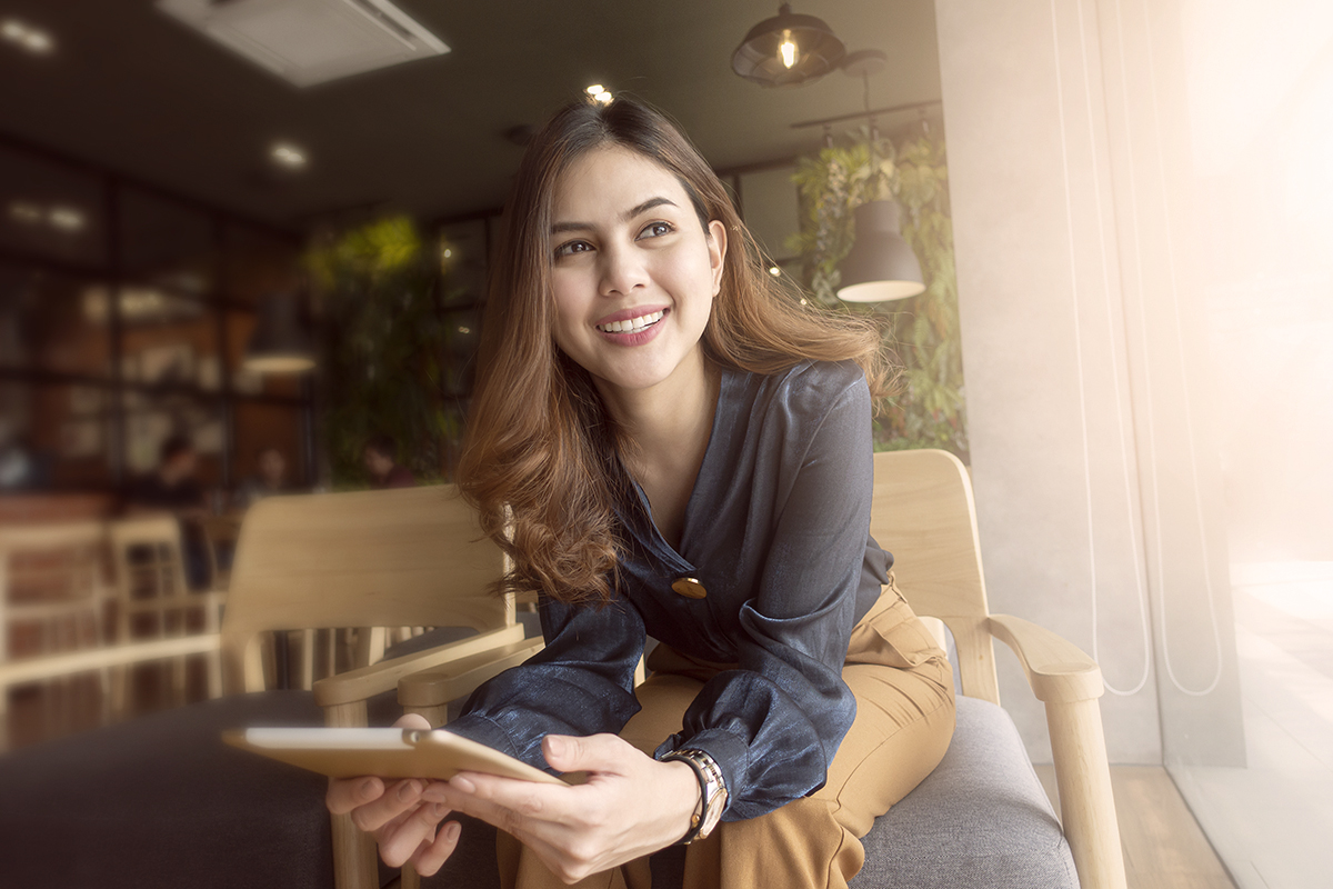 Beautiful woman is working with tablet in coffee shop